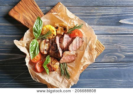 Tasty juicy meat with vegetables on wooden board