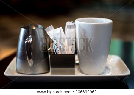 Sugar packets cream and coffee on tray for breakfast