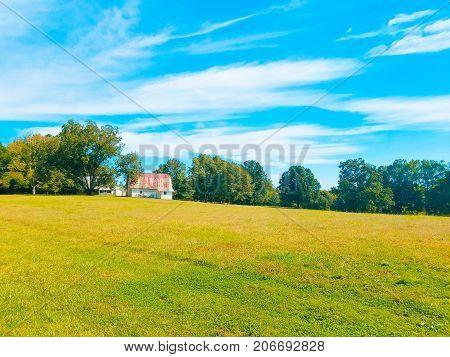 A rusty old barn on a grassy hill under a blue sky.
