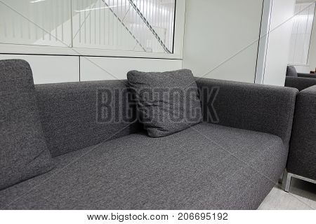 Dark grey fabric sofa in waiting room or contemporary office interior with lounge area workplaces or public area. empty room.