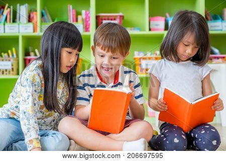 Children sitting on floor and reading tale book in preschool libraryKindergarten school education concept