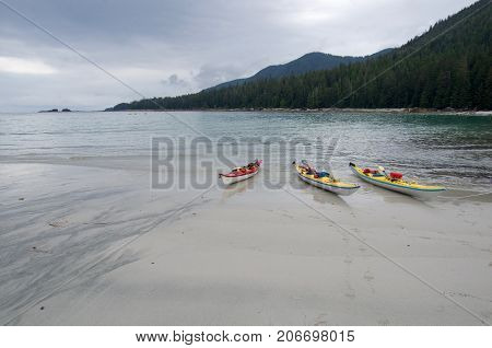 Three sea kayaks pulled up on a sandy beach on the Brookes peninsula Vancouver Island. Gray cloudy sky.
