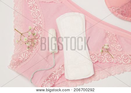 Hygienic tampon and sanitary napkin for every day with pink and white panties with green flowers on a white background