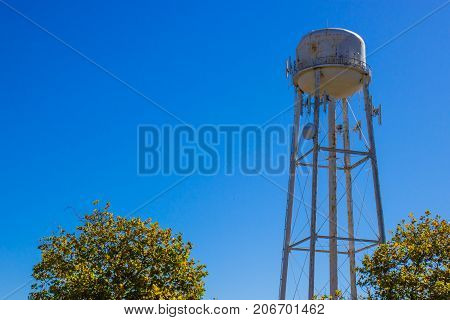 Old Rusted Water Tank Tower Above Treeline