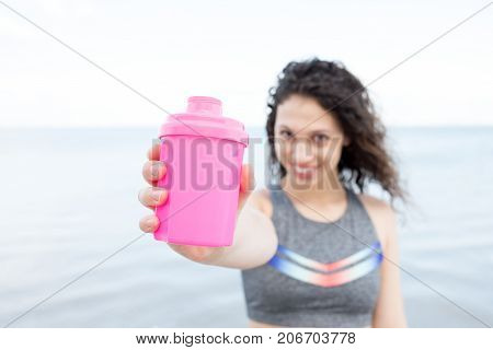 Closeup portrait of smiling young attractive woman looking at camera, wearing sportswear and offering drink in plastic shaker with river in background and focus on shaker. Front view.