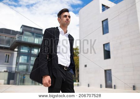 Ambitious confident businessman looking forward and thinking of success. Purposeful serious manager walking over downtown district. Student of business school concept