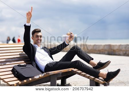 Energetic businessman enjoying work on trip and sitting on comfortable wooden bench. Emotional successful young man using smartphone and looking at camera. Winning concept