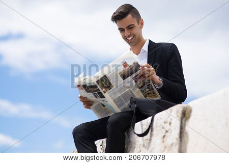 Excited student always knowing actual news. Happy young trader monitoring world news reading newspaper outdoors. Modern businessman concept