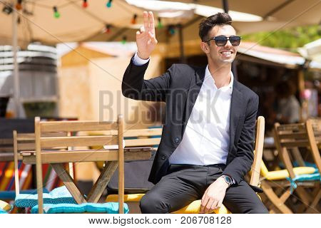 Happy carefree man waving with fingers to waiter asking him to come. Cheerful handsome businessman having lunch break in outside cafe in Portuguese. Break concept
