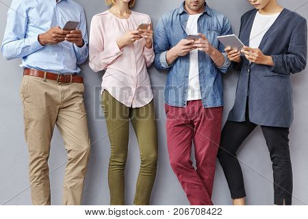 Cropped Shot Of Diverse Friends Use Digital Devices, Stand Next To Each Other, Wear Formal Clothes,