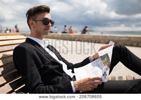 Positive young businessman enjoying stroll after work. Pensive relaxed guy in formalwear reading newspaper while sitting on bench outdoors. Modern business concept