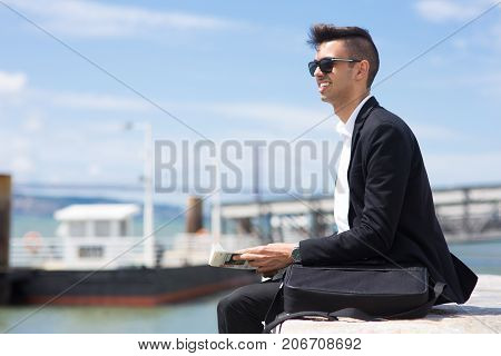 Purposeful young man deep in thoughts resting on pier and dreaming of success. Smiling handsome student with briefcase reading newspaper outdoors. Contemplation concept