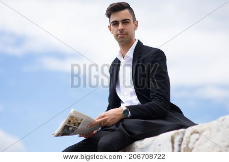 Serious ambitious young man holding newspaper and looking at camera outdoors. Confident student searching job in newspaper. News concept