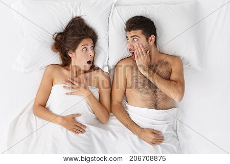Lovers In Bed Look With Terrified Expression At Each Other As Hear That Someone Came In House, Being