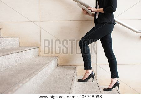 Portrait of young Caucasian businesswoman wearing high-heeled shoes walking upstairs and using digital tablet. Business concept