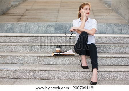Portrait of displeased young Caucasian businesswoman holding glasses sitting on stairs with documents, coffee cup and calculator. Work life balance, unemployment concept