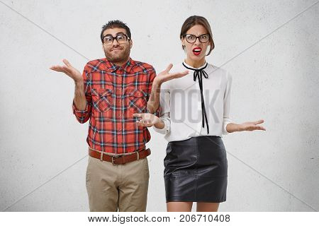 Indoor Shot Of Uncertain Man And Woman In Formal Clothes Shrug Shoulders, Don`t Know Answer Or Way O