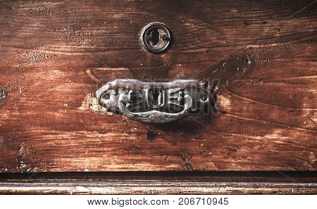 Vintage cabinet made of wood. Old metal door handle