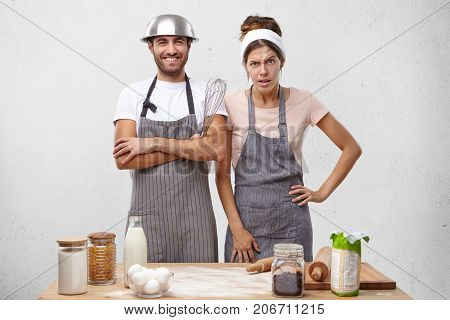 Portrait Of Indignant Female Cook Keeps Hand On Waist, Going To Have Quarrel With Colleagues, Stands