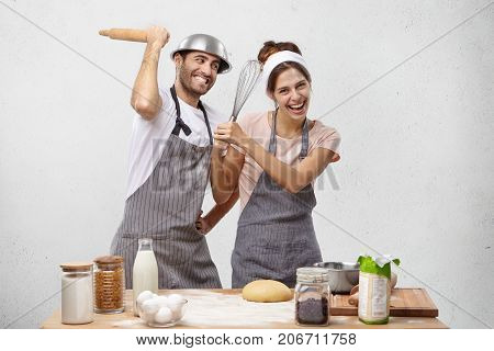 Overjoyed Male And Female Have Funny Fight At Kitchen, Threaten With Rolling Pin And Whisk, Make Fun