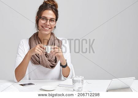 Glad Businesswoman Wears White Blouse With Scarf And Glasses, Sits At Office Desk, Holds Cup Of Coff