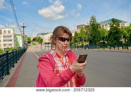 Woman in unfamiliar city trying to find her location with smartphone