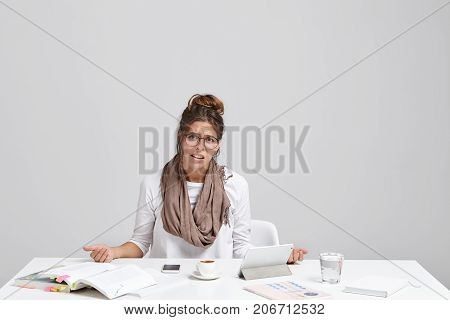 Portrait Of Discontent Tired Young Beautiful Businesswoman Sits At Office Desk, Drinks Espresso, Wor