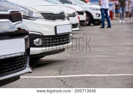 Closeup of new cars standing in row on outdoor parking