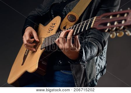 Guitar with woman's hands playing the guitar on the dark background