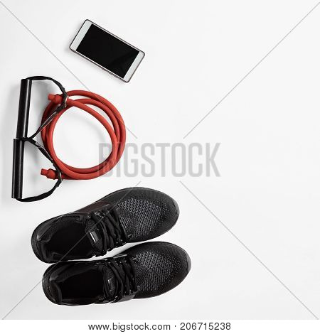 Athlete's male set with mobile phone, elastic expander and gymshoes, image with Square ratio