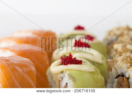 Sushi rolls with avocado and tobiko caviar and philadelphia rolls. Macro. Photo can be used as a whole background.