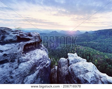 Spring morning nature. The cracked sandstone cliff above forest valley daybreak Sun at horizon. Hills increased from misty background