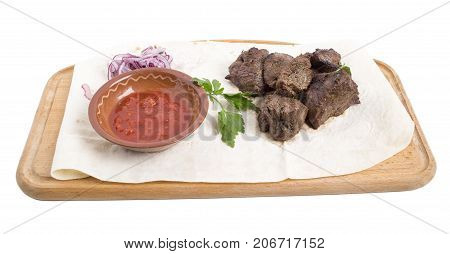 Sliced beef steak with tomato sauce and red onion on a wooden board. Isolated on a white background.