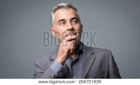Smart Businessman Thinking With Hand On Chin