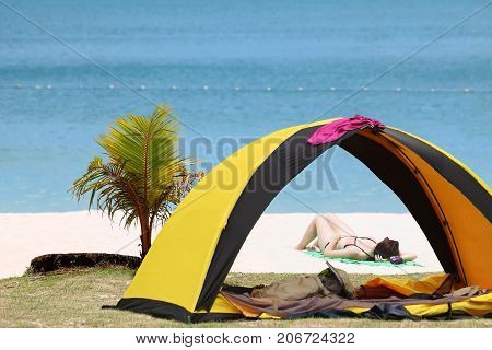 Women camping and relaxing near the tent on the coconut beach Teen girl in bikini travel on samui island Thailand.