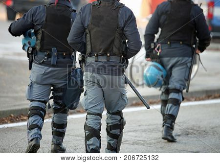 Three Policemen With Anti-bulletproof Jacket In Anti-riot Unifor