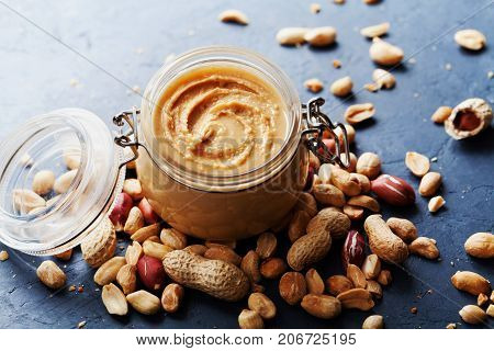 Peanut butter jar and heap of nuts on dark rustic background.