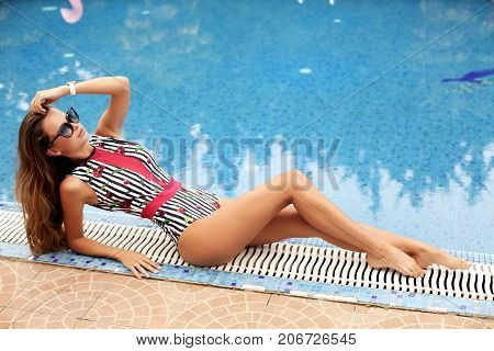 Beautiful Woman With Dark Long Hair In Swimming Suit, Relaxing Near Swimming Pool
