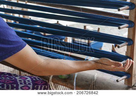 Local woman Weaver binding thread on wooden stand before weaving