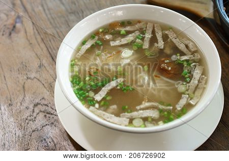 Delicious traditional Vietnamese noodle soup with Vietnamese pork sausage served in a bowl on wooden table typical food in Ubon Ratchathani Thailand