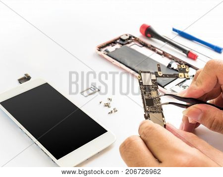 Close-up of technician hand clamping processor on smartphone logic board on smartphone component background with copy space