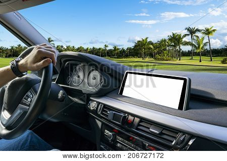 Male hands holding car steering wheel. Hands on steering wheel of a car driving near the palm. Man driving a car inside cabin. Multimedia system isolated white blank screen. Copy space