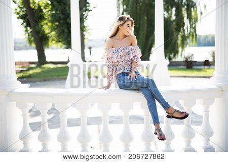 Beautiful Young Brunette Woman Sitting On Handrail In Park