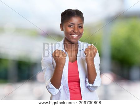 Cheering young african american woman with casual clothes outdoors