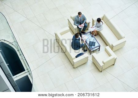 Directly above view of concentrated managers in formalwear analyzing financial figures while having informal working meeting at modern spacious office lobby
