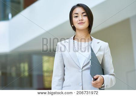 Waist-up portrait of attractive young white collar worker looking at camera with warm smile while standing at spacious office lobby