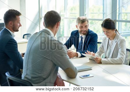 Cheerful group of white collar workers having fun while working together on promising start-up project, interior of modern boardroom with panoramic windows on background
