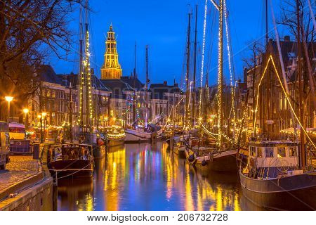 Historic sailing ships moored at river quay on the annual Winterwelvaart festival around christmas. Reliving the old times in the historic part of Groningen city.
