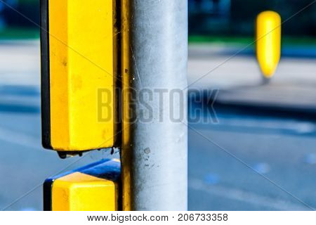 pedestrian crossing equipment in UK, with blurred pedestrians in the background.