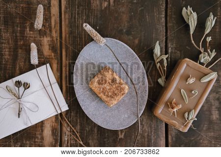 Top close up view of still life with handmade organic rustic soap with dried flowers soap-dish and little white cute romantic envelope on dark wooden table background.